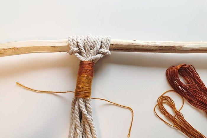 3. Nouer un fil à broder sur tous les fils et les entourer pour créer un tissage coloré. Répéter cette action avec une autre couleur de fil à broder.