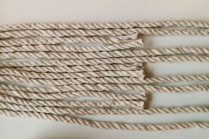 1. Coupez 3 longueurs de 40 cm et 4 longueurs de 1,50 m de fil macramé 6 mm blanc, 1 longueur de 3 m de fil de jute 4 mm, 2 m et 3 m de fils à broder de 2 couleurs différentes (tons ocre jaune et ocre rouge). 4 longs pompons seront nécessaires pour la création.