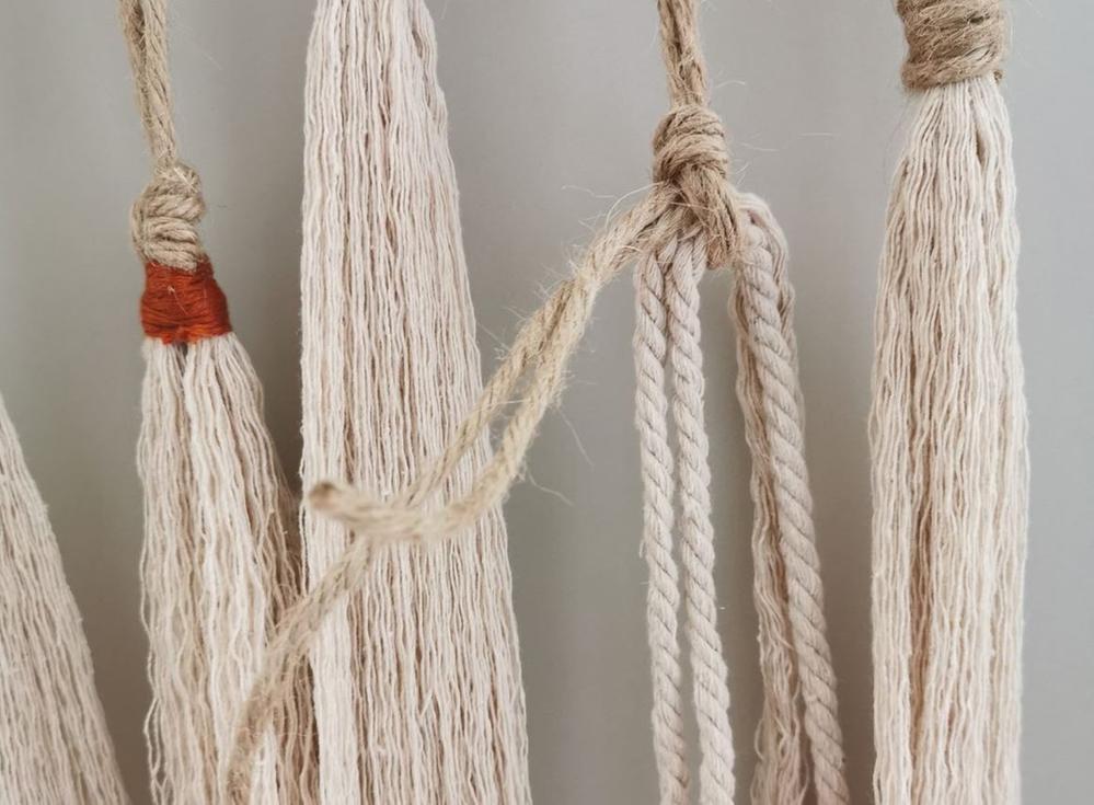 15. Suspendre au bout des fils de jute 3 longueurs de fil macramé blanc pliées en deux pour créer un long pompon. Serrer et nouer un fil de broderie pour entourer le sommet et réaliser une jolie finition avec les fils de jute. Peigner et égaliser aux ciseaux les fils pour obtenir un pompon d'environ 10 cm.