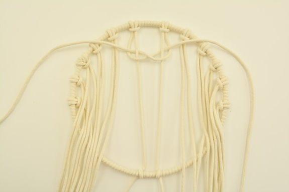 ETAPE 2/9 Les espacer harmonieusement puis fixer à l'aide du nœud demi-clé* les deux fils centraux en bas du cercle. Réaliser un demi nœud plat sur ces deux fils tendus.