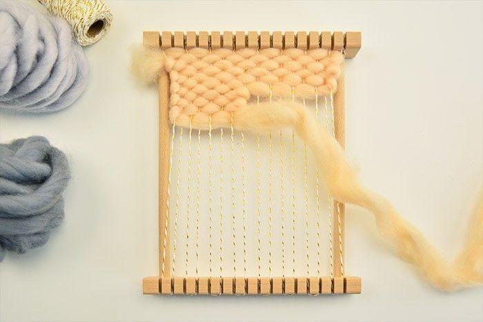 ETAPE 1/9 Préparer le montage du métier à tisser avec la ficelle bicolore, en suivant les étapes indiquées sur l'emballage. Débuter le tissage avec 1,80 m de laine vieux rose et débuter le point de toile : passer la laine entre la trame de fils, une fois dessus, une fois dessous sur 6 rangs complets, puis 4 moitiés.