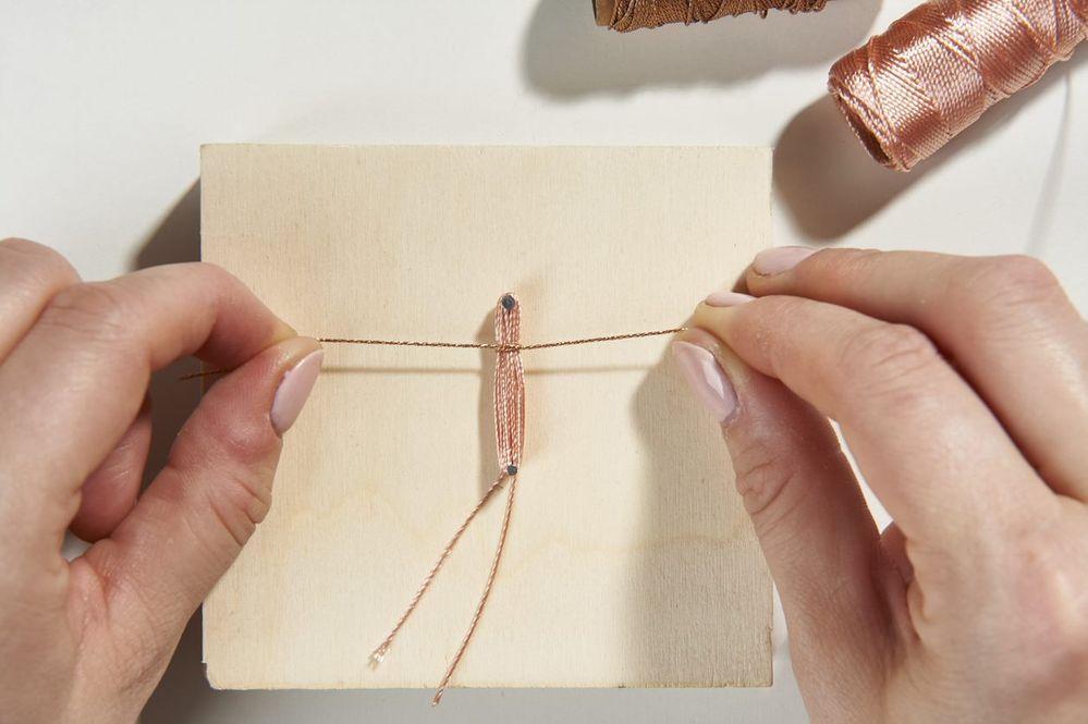 ETAPE 2/10 Enrouler sur 20 tours le fil effet de soie rose puis réaliser un double nœud avec le fil cuivre afin qu'il serre tous les fils roses et crée une petite boucle au sommet (suspension du pompon). Astuce : déposer une pointe de colle à bijoux pour fixer le nœud si besoin.