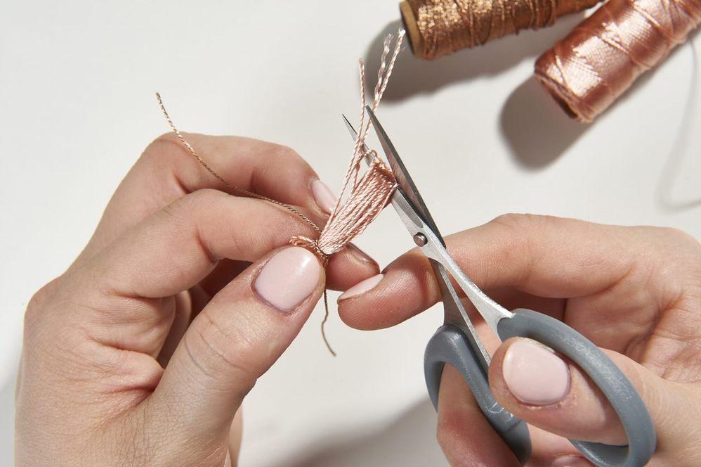 ETAPE 3/10 Défaire le pompon des clous et égaliser les longueurs avec des ciseaux de précision. Finaliser le pompon en enroulant sur plusieurs tours le fil cuivré. Terminer par un double nœud. Réaliser 5 pompons par boucle d'oreilles en suivant les étapes précédentes. Les insérer sur le pendentif.