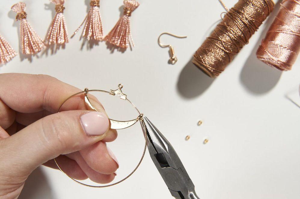 ETAPE 5/10 Insérer ensuite une perle à écraser puis enfiler le second anneau de la breloque « croissant ». Centrer la breloque et écraser la perle avec la pince à bijou plate pour que la breloque ne bouge plus sur la partie droite.
