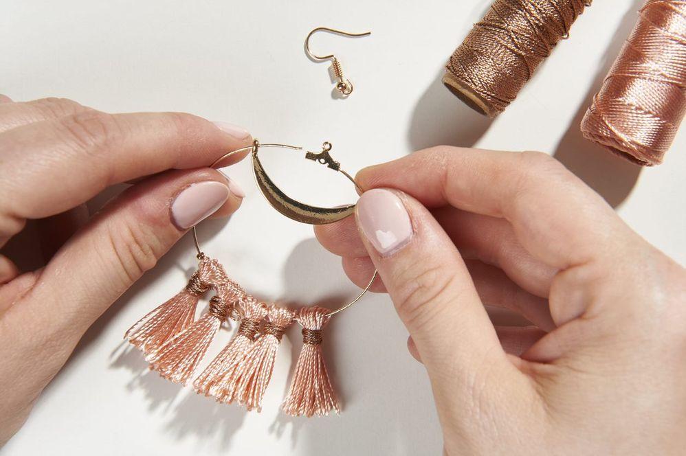 Tirer sur la base ronde du pendentif pour l'ouvrir et y insérer l'anneau droit de la breloque « croissant ».  Boucles d'oreilles créoles - étape 5 ETAPE 5/10 Insérer ensuite une perle à écraser puis enfiler le second anneau de la breloque « croissant ». Centrer la breloque et écraser la perle avec la pince à bijou plate pour que la breloque ne bouge plus sur la partie droite.  Boucles d'oreilles créoles - étape 6 ETAPE 6/10 Retirer le second anneau de la breloque de la base du pendentif, insérer les 5 pompons réalisés précédemment, une perle à écraser puis à nouveau l'anneau de la breloque « croissant ». Refermer la base ronde du pendentif.