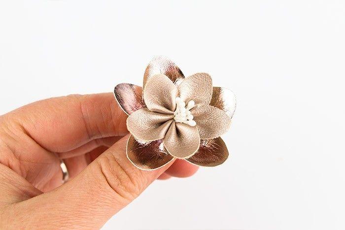 ETAPE 7/10 Prenez quelques pistils que vous allez plier en deux. Passez l'extrémité pliée dans le trou et tirez sur les pistils pour les positionner à votre goût. Collez pour maintenir en place.Collez la petite fleur sur la grande en alternant les pétales. Veillez à ce que l'ouverture centrale soit bien l'une au dessus de l'autre. Laisser sécher.