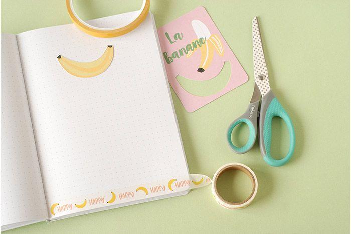 IDÉE N° 3 : CRÉATION D'UN MOOD TRACKER (OU HUMEUR DU JOUR) Découper une banane dans une carte de la collection et la coller à l'aide d'adhésif double face sur une page du carnet. Coller du masking tape au bas de la page et laisser déborder pour pouvoir le replier et en faire un onglet.
