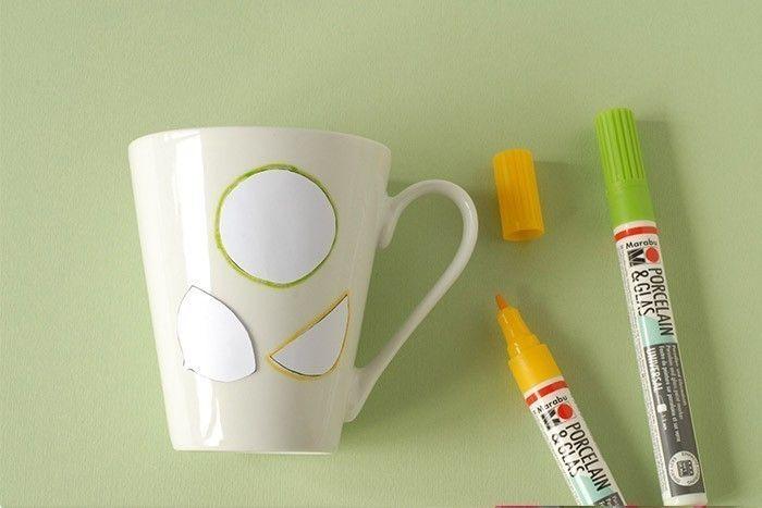 ETAPE 2/7 Fixer la rondelle de citron vert puis la tranche de citron jaune et le demi citron jaune. Dessiner le contour du citron vert au feutre porcelaine vert en suivant le contour du gabarit. Laisser sécher. Dessiner les contours des autres citrons au feutre jaune. Laisser sécher. Ôter les gabarits. Astuce : Si la couleur a un peu bavé, gratter avec un cure-dent.