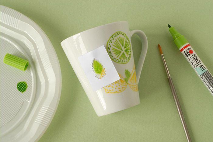 ETAPE 5/7 Prendre le gabarit de la feuille de menthe. Tapoter plusieurs fois le feutre dans une assiette en plastique pour faire descendre la peinture. Encrer le pinceau plusieurs fois pour le charger de couleur. Peindre la feuille de menthe sur la tasse en s'aidant du gabarit mais sans le suivre exactement. Peindre 2 ou 3 couches de vert pour obtenir la teinte voulue. Varier les tailles des feuilles. Laisser sécher.