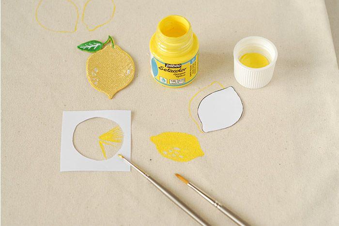 ETAPE 3/8 Prendre le gabarit des rondelles de citron. Le placer sur le sac. Peindre le contour au pinceau fin et à la peinture textile jaune. Peindre les pulpes. Laisser sécher. Peindre plusieurs rondelles de citron jaune répartis sur l'ensemble du sac.