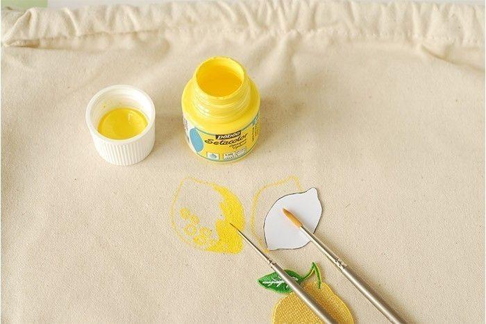 ETAPE 2/8 Télécharger et imprimer les gabarits et les découper. Placer le gabarit d'un citron sur le sac. Peindre le contour au pinceau fin et à la peinture textile jaune. Tracer des ronds pour figurer l'écorce et peindre autour jusqu'à remplir le citron. Peindre plusieurs citrons jaunes de cette façon. Laisser sécher.