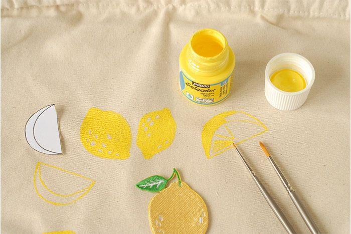 ETAPE 4/8 Prendre le gabarit des quartiers. Le placer sur le sac. Peindre le contour au pinceau fin et à la peinture textile jaune citron. Peindre l'écorce et dessiner les pulpes. Laisser sécher. Peindre plusieurs quartiers de citron répartis sur le sac. Laisser sécher.