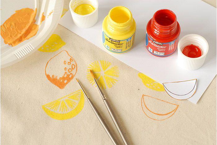 ETAPE 5/8 Préparer la couleur orange en mélangeant du jaune et du rouge vermillon. Peindre des fruits oranges répartis su l'ensemble du sac de la même façon que pour les citrons jaunes. Laisser sécher.