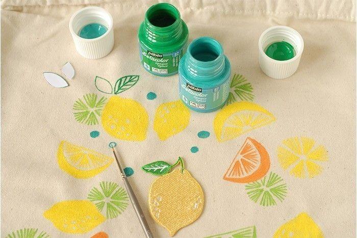 ETAPE 7/8 Peindre les feuilles vertes en s'aidant des gabarits. Ajouter les nervures. Terminer en peignant des pois bleu turquoise de tailles différentes répartis sur le sac. Laisser sécher. Fixer en repassant les motifs au fer à repasser.