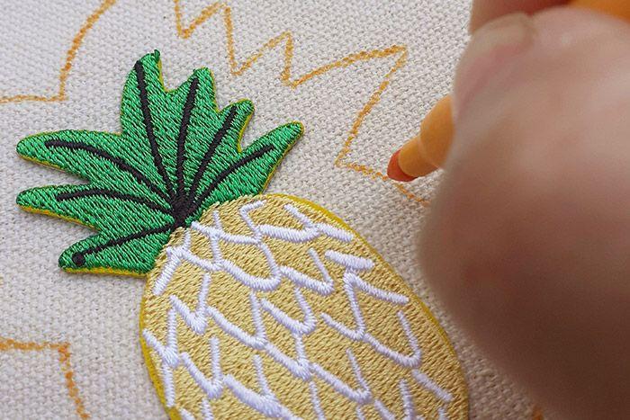 ETAPE 2/5 Tracer le contour des motifs au feutre, ici un feutre orange pour rester dans le même ton que le fil de broderie, ou utilisez un feutre effaçable. Vous pouvez également ajouter du lettering pour personnaliser le sac avec d'autres broderies (voir gabarit)