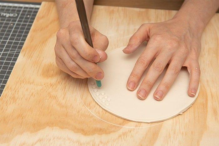 ETAPE 4/9 A l'aide du manche du pinceau façonner des petits ronds dans l'argile pour imiter l'effet corail.