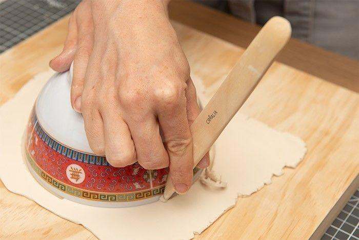 ETAPE 3/9 Retourner le bol sur l'argile et découper le rond du bol à l'aide d'un ébauchoir en bois. Oter le surplus d'argile.