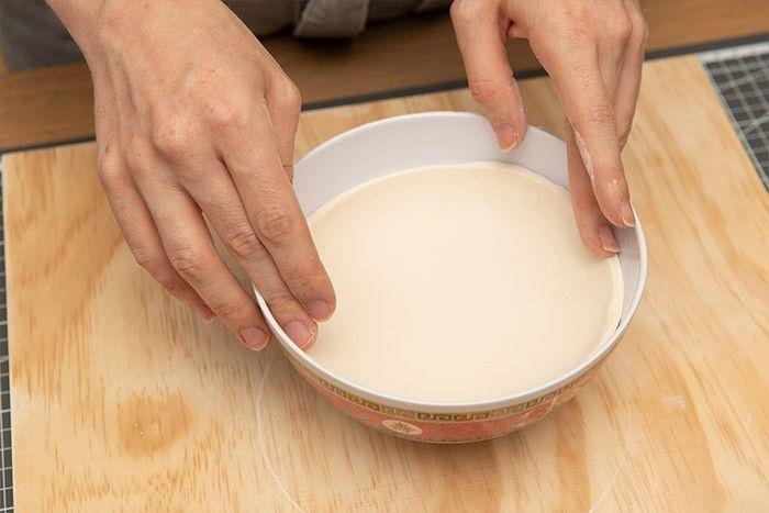 ETAPE 5/9 Décoller délicatement l'argile de la planche et venir la déposer dans le bol afin qu'il prenne la forme d'une coupelle. Attention placer la face façonnée contre le bol. Laisser sécher 24h. Une fois l'argile sèche retirer la coupelle du bol en acier.