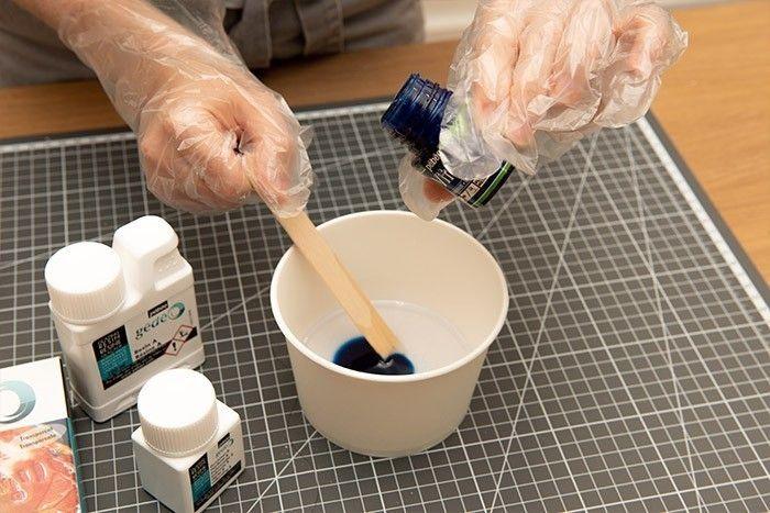 ETAPE 6/9 En suivant les instructions du fabricant préparer la résine de glaçage. Une fois le mélange réalisé, ajouter une douzaine de gouttes de peinture vitrail bleu profond. Mélanger à nouveau votre résine.