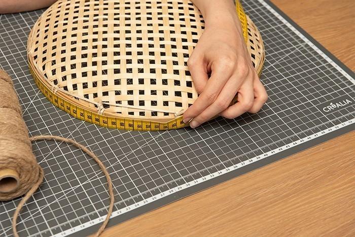ETAPE 5/9 Prendre la mesure du contour du panier rond plat tressé à l'aide d'un mètre ruban (environ 95 cm). Couper cette longueur dans le fil de jute en y ajoutant 15 cm.