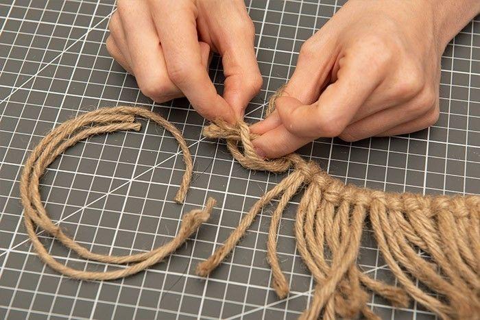 ETAPE 6/9 Couper des longueurs de 20 cm dans le fil de jute. Plier une longueur en deux. Glisser sous la corde et passer les deux extrémités dans la boucle, serrer. Répéter l'opération pour recouvrir la ficelle sur 95 cm.