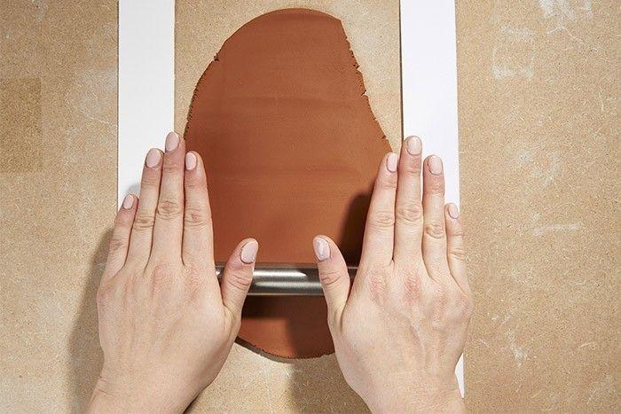 ETAPE 1/5 Etaler l'argile autodurcissante sur une planche en bois à l'aide d'un rouleau. Astuce : Pour obtenir une épaisseur égale, positionner deux planchettes de chaque côté du rouleau.