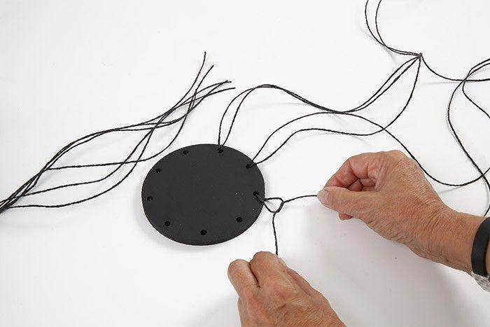 ETAPE 1/7 Peindre le socle en noir. Laisser sécher. Pour obtenir une corbeille de 8 cm de haut, couper 9 longueurs de ficelle d' 1 m et nouer chacune dans chaque trou du socle de façon à obtenir 2 longueurs égales.