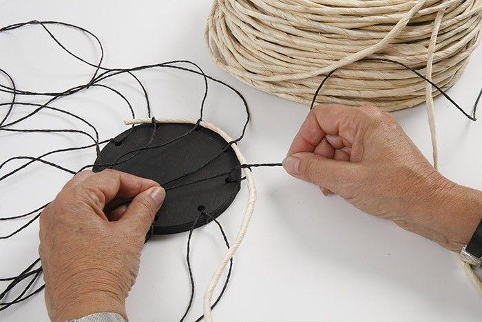 ETAPE 2/7 Disposer une extrémité de la corde de maïs sur un premier trou, nouer avec la ficelle puis recommencer cette étape à chaque trou suivant pour fixer la corde. S'assurer qu'au démarrage la corde est bien positionnée au ras du socle.