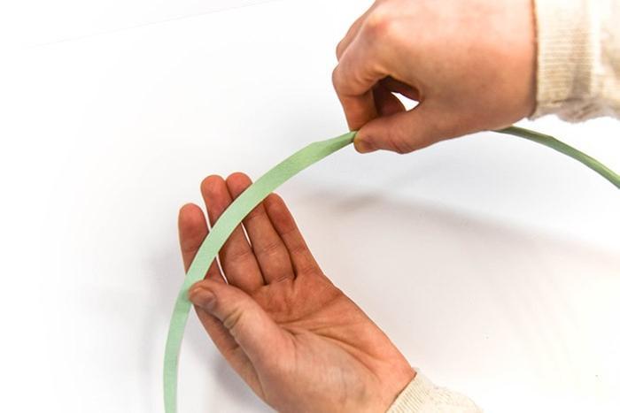 ETAPE 4/13 Repliez-la autour de la moitié du cerceau, en pinçant les bords pour qu'ils soient bien sécurisés. Ce bord servira de base pour coller facilement vos feuilles en papier.