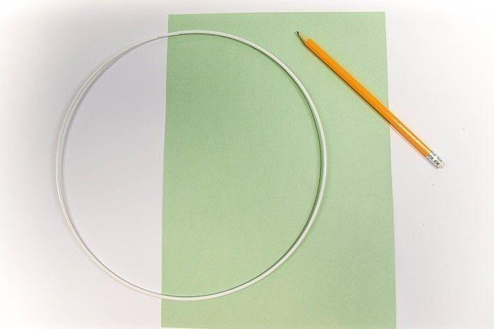 ETAPE 2/13 Tracez le contour interne et externe de la moitié de l'anneau sur du papier cartonné vert au crayon de papier, et découpez la demi-lune en laissant assez de place de part et d'autre pour pouvoir la replier autour de l'anneau.