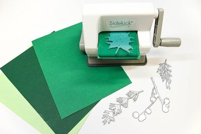ETAPE 1/13 Avec la Machine Sizzix® Sidekick™ Starter Kit et les matrices de découpe Feuilles Naturelles, découpez plusieurs feuilles en utilisant les différents tons de papier cartonné vert.
