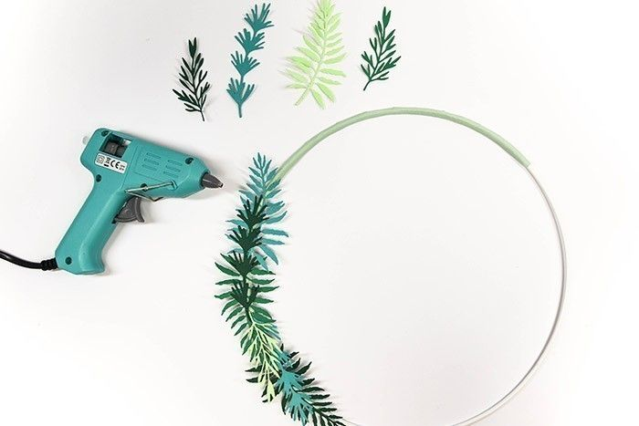ETAPE 5/13 Arrangez les différentes feuilles découpées sur la partie de l'anneau recouvert de papier et collez les éléments au pistolet à colle.