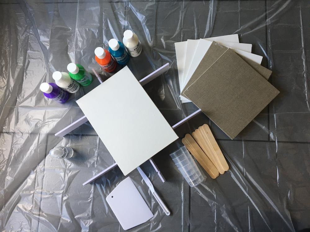 Le matériel : bâche de protection, support élévateur pour la toile, carton toilé, huile de silicone, couteaux à peindre et raclette, gants, verres, bâtonnets en bois pour mélanger, acryliques fluides Pouring