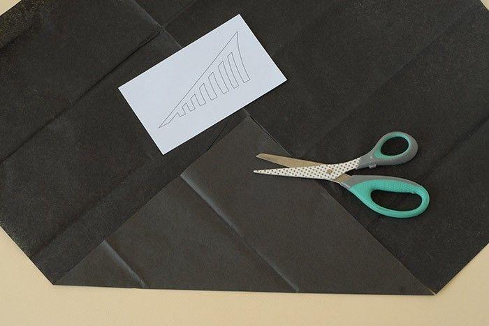 ETAPE 4/7 Les toiles d'araignée. Prendre une feuille de papier de soie noir. Replier une pointe en suivant le pli central de la feuille pour former un carré. Découper.