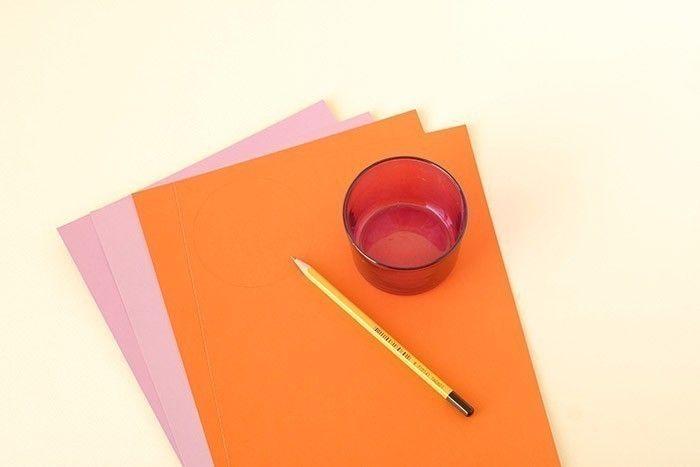 1. Choisir 2 feuilles de Cartoline orange à dos violet et 2 feuilles de Cartoline mauve à dos violet. Prendre un verre et tracer le contour 10 fois sur le papier orange et 10 fois sur le papier mauve.