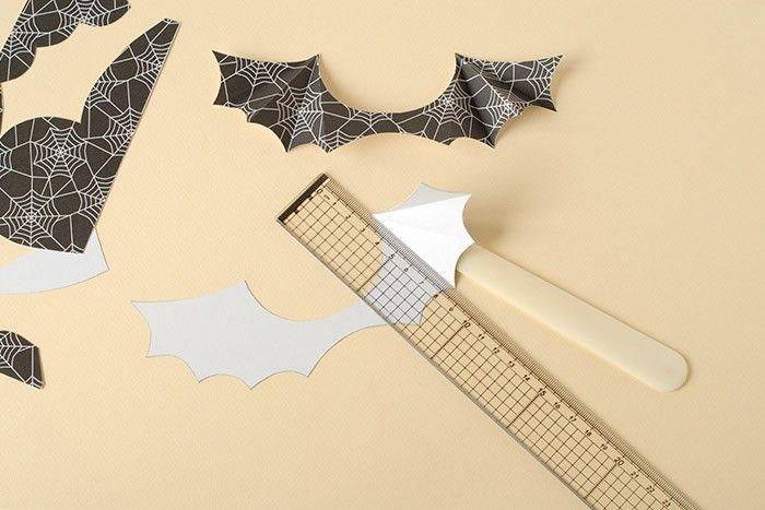 ETAPE 4/7 Découper les ailes et marquer les plis : positionner la règle à l'endroit du pli et faire glisser le plioir sous le papier. Appuyer contre le bord de la règle pour relever le papier et marquer le pli. Faire de même pour chaque pli. Plier ensuite les ailes en accordéon.