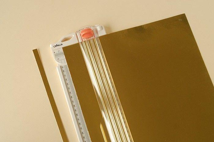 ETAPE 2/7 Découper au massicot une bande de papier or de 1 cm de large. Découper une bande de 6 cm de large.