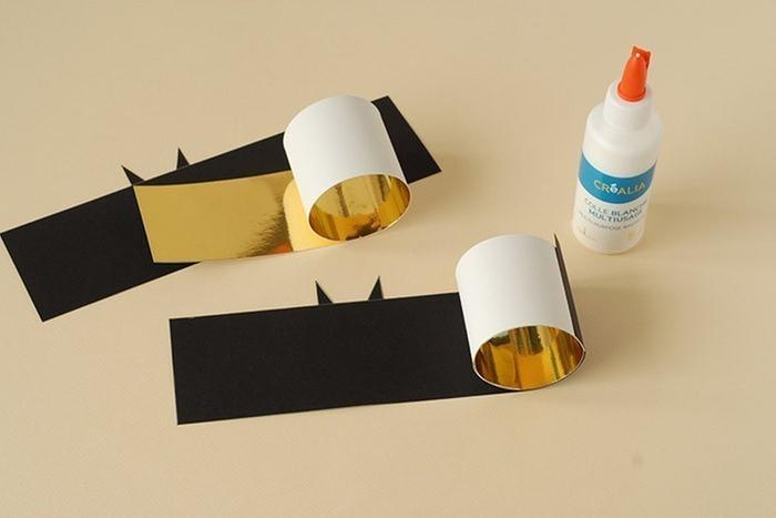 ETAPE 3/7 Rouler la bande de papier or sur elle-même pour former un cylindre de 5,5 cm de diamètre environ. Coller. Coller par dessus le papier noir. Laisser sécher.