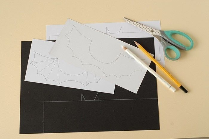 ETAPE 1/7 Imprimer les gabarits des emballages. Reporter le corps sur une feuille de papier noir au crayon blanc. Reporter les ailes au dos d'une feuille de papier à motifs toile d'araignée.