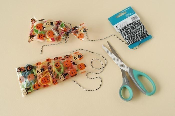 ETAPE 6/7 Garnir les sachets de bonbons. Nouer avec un morceau de ficelle bicolore. Déposer dans les emballages.