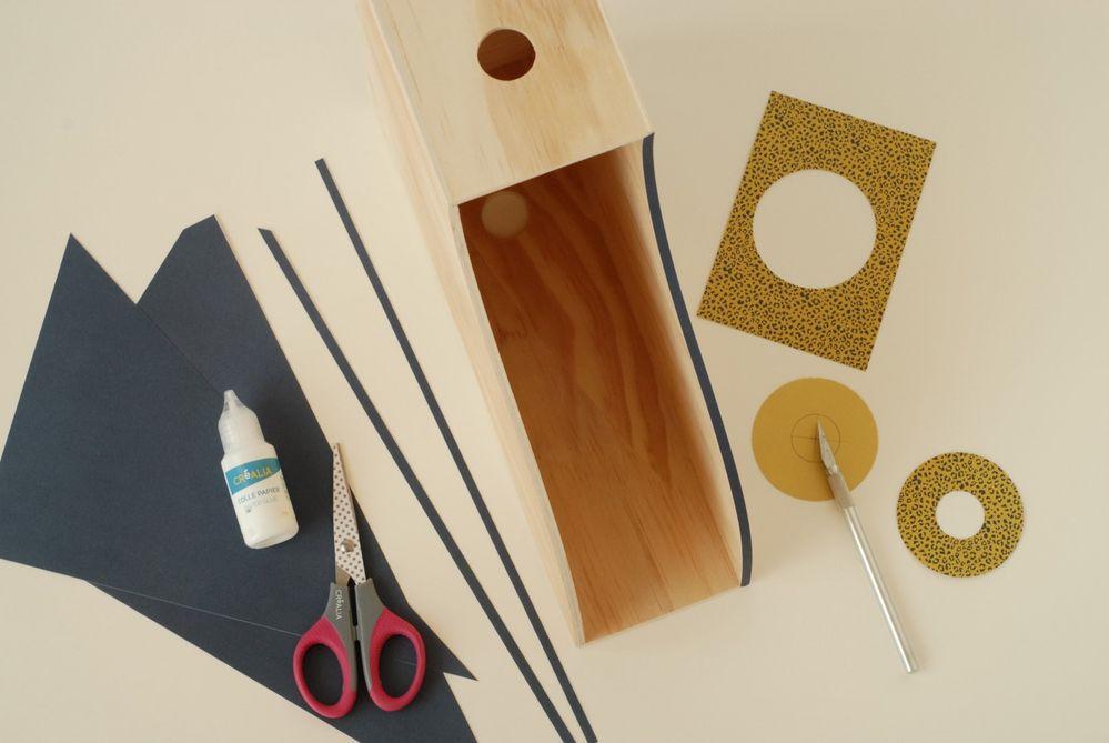 5. Couper 4 bandes de 0,5 cm de large dans la diagonale d'une feuille de papier bleu marine. Découper un disque de 65 mm de diamètre sur une feuille de papier tigre (voir gabarit) Evider le centre.