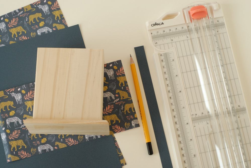 Le pot à crayon 6. Mesurer la hauteur du pot. Couper une feuille de papier à motifs. Couper une bande de papier bleu marine de 1,5 cm de large.