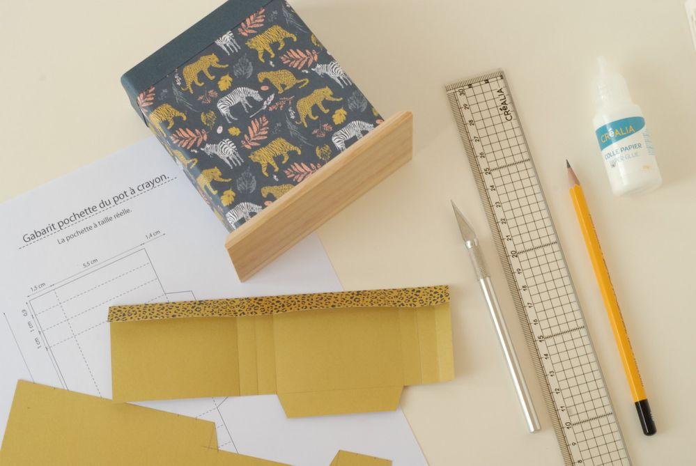 7. Coller sur le pot. Coller la bande pour faire un revers. Reporter les mesures de la pochette (voir gabarit) sur une feuille de papier tigre bicolore. Marquer les plis.