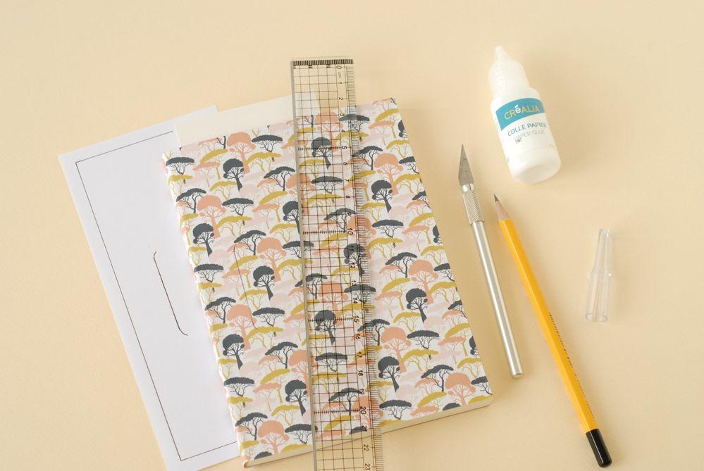 2. Coller sur la couverture du carnet. Imprimer le gabarit de la fente. Reporter sur le carnet. Glisser une chute de carton (ou un tapis de découpe) sous la couverture puis couper au cutter à l'aide de la règle.