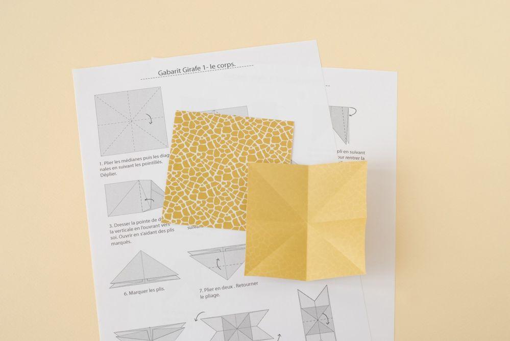 5. Télécharger et imprimer les schémas explicatifs de l'origami girafe. Prendre une feuille de papier origami 5 x 5 cm. Faire le pliage du corps.
